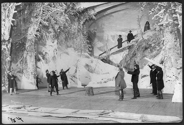 "Scene from stage production of ""Uncle Tom's Cabin"", 1901)- group of men, two holding whips, pointing at two men and a woman on snow-covered bridge LCCN2004681922"