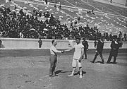 Schuhmann (left) and Georgios Tsitas shake hands before the final match of the wrestling competition.