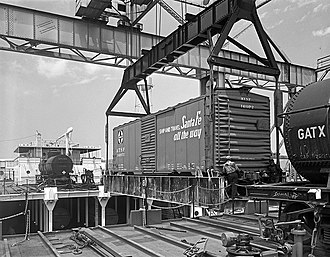 Seatrain Lines - The specialist crane hoist the cradle loaded with an ATSF boxcar from the Seatrain Louisiana.