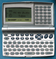 Sharp YO-520 organizer, inside, power on displaying date and time, on blue background (30421189914).png