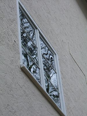Soda-lime glass - Old window made from soda-lime flat glass, Jena, Germany: The distorted reflections of a tree indicates that the flat glass was possibly not made by the float glass process.