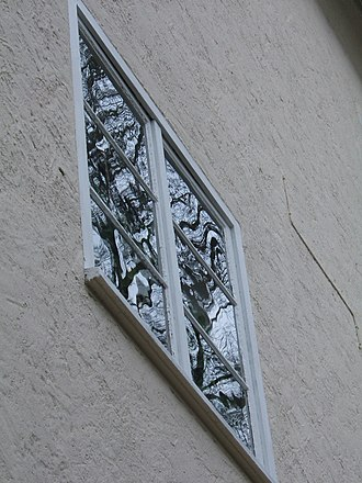 Soda–lime glass - Old window made from soda-lime flat glass, Jena, Germany: The distorted reflections of a tree indicates that the flat glass was possibly not made by the float glass process.