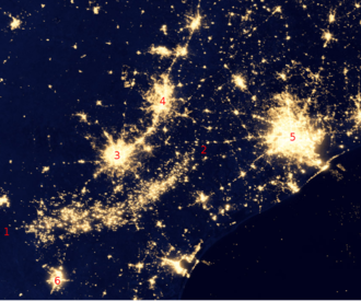 "Oil field - Eagle Ford Shale flares visible from space (green and infrared wavelengths), in the arc between ""1"" and ""2"", amid cities in southeast Texas in 2012."