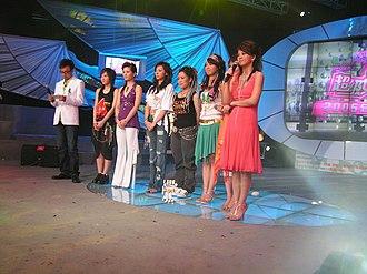 Super Girl (TV series) - Six finalists during a 2005 national round event in Changsha, Hunan.From right to left: host Li Xiang, contestants Lin Shuang, She Manni, Yi Hui, Zhang Liangying, Guo Huimin, Li Na, and host Wang Han.