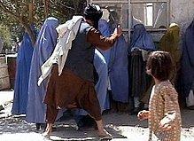 A Taliban religious policeman beating a woman because she removed her burqa in public.