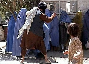 Islamic religious police - Kabul, 2001, image obtained by the Revolutionary Association of the Women of Afghanistan showing a religious policing member responsible for promotion of virtue and prevention of vice enforcing Sharia rules on a woman for removing her burqa headpiece in public.