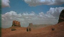 A color screenshot of several men on horses, in three groups: Native Americans on the left, Americans in the center, and Native Americans on the right. The men are located in a desert and in the background are large rock formations and blue skies with white clouds.