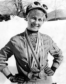 A smiling short-haired blond woman wears a track suit with gloves, and a hat with white skiing goggles. She holds her hands on her waist and carries two medals around her neck. Behind her, a sunny and snowy landscape.
