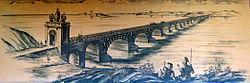 Am artist's interpretation of Trajan's Bridge depicted upon a light brown surface, with bridge stretching from near shore of river on the bottom left and the far shore in the top right.