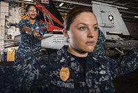 U.S. Navy Operations Specialist 3rd Class Shauntelle Rhanes, left, practices weapons retention procedures with Master-at-Arms 1st Class Sara Horvath in the hangar bay of the aircraft carrier USS Nimitz (CVN 68) 130826-N-TW634-106.jpg