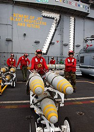 US Navy 030114-N-4965F-509 Aviation Ordnancemen stand in front of the ship's island with 1000 pound MK-83 bombs.jpg