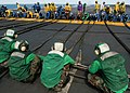 US Navy 040422-N-4190W-002 Air department personnel stretch the emergency barricade ropes to position.jpg