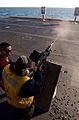 US Navy 050121-N-5345W-138 Gun smoke pours from the barrel of an M-240 machine gun as a Sailor participates in a weapons qualification aboard the Nimitz-class aircraft carrier USS Harry S. Truman (CVN 75).jpg