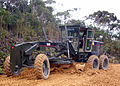 US Navy 060225-N-9830P-007 Equipment Operator 3rd Class Mathew Westcott assigned to Naval Mobile Construction Battalion Four (NMCB-4), operates a grader during road construction at the Jungle Warfare Training Center.jpg