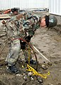 US Navy 070302-N-6247M-017 Construction Electrician Constructionman Joshua Gonzales, from San Diego, Calif., pulls up old wires outside a prefabricated building his unit is working on.jpg