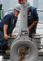 US Navy 071107-N-0807W-038 Mineman Seaman Casey Faires stationed aboard the mine warfare ship USS Patriot (MCM 7), helps guide the anchor chain, as the ship moors to a buoy in waters just off the coast of Hong Kong.jpg
