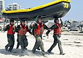 US Navy 090527-N-4301H-006 First-phase Basic Underwater Demolition-SEAL (BUD-s) candidates balance a small inflatable boat on their heads while heading toward the Pacific Ocean.jpg