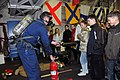 US Navy 100505-N-9917S-005 Damage Controlman 2nd Class Gabriel Johnson demonstrates firefighting techniques to students from Klaipeda Gilijos Primary School aboard the guided-missile cruiser USS Vicksburg (CG 69) in Klaipeda, L.jpg