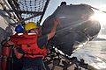 US Navy 101111-N-7293M-778 Boatswain's Mate Seaman Dustin Holroyd and members of the deck department guide a 7-meter rigid hull inflatable boa.jpg
