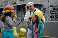 US Navy 110727-N-OB313-070 Damage Controlman 3rd Class Andrew Perez, assigned to the mine countermeasures ship USS Champion (MCM 4), helps children.jpg