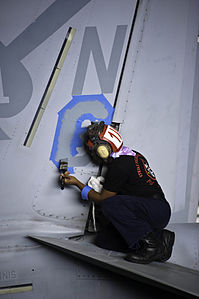 US Navy 120206-N-GC412-466 Airman James Rice paints the squadron designator on the vertical stab on an F-A-18F Super Hornet from the Black Aces of.jpg
