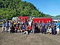 US officials and local fishers pose in front of a red fire engine in American Samoa.jpg