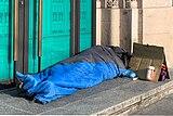 Un sans-abri dans un duvet dans le centre-ville de Lausanne (Suisse).jpg