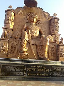 Large statue of a seated Vikramaditya, holding a sword