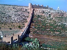 A line of square towers, connected by walls and topped with battlements (protective protrusions), spans the bottom to the top of a mountain slope.