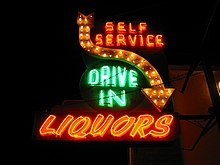 "A green and orange neon sign that says ""self service drive in liquors,"" and has an arrow pointing downward."