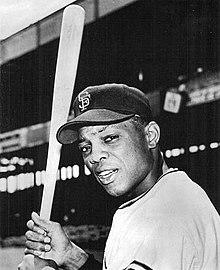 Fotografie a lui Mays cu SF pe șapca neagră privind spre cameră ținând un liliac în partea dreaptă, cu o tribună de baseball în fundal