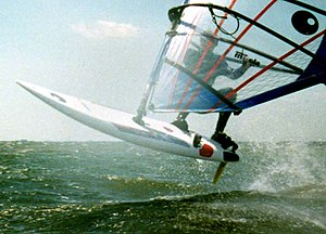 Windsurfing - A windsurfer using an early 1990s slalom board to perform a small jump.