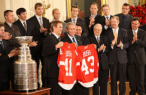 "In the front row, Nicklas Lidstrom holds a Red Wings jersey with the last name ""BUSH"" and the number ""41"" while George W. Bush holds a Red Wings jersey with the last name ""BUSH"" and the number ""43"".  To Lidstrom's right is the Stanley Cup.  2nd row, left to right: Mike Babcock, Ken Holland, Jim Devellano, Jim Nill, unknown man.  Third row, left to right: Kris Draper, Pavel Datsyuk, Mikael Samuelsson, Brian Rafalski, Derek Meech, Kirk Maltby, Chris Osgood, Aaron Downey."