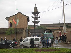 Linxia City - Worshippers leaving a small mosque in Linxia City, on foot, by truck and bus