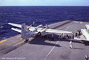 A twin propeller aircraft is sitting at the start of an aircraft carrier's catapult. Several people are either working on the aircraft, or observing