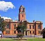 Double storey red brick building with centrally placed tower and decorative sandstone detail, including sandstone portico on front façade. Timber doors and windows. Market hall at rear of building with corrugated iron roof and verandah. The building was erected by the builders Kelly and Anderson of Johannesburg. The cornerstone was laid on 2 August 1907 by Sir Hamilton Goold-Adams, Lieutenant-Governor of the Orange River Colony. The building was officially inaugurated on 7 September 1908. Architectural style: Neo-classical. Type of site: Town Hall Current use: Town Hall. This red brick building with its sandstone ornamentation was designed by Price and Agutter and erected in 1907-1908. It is one of the most impressive town halls in the Free State and a landmark in Harrismith.
