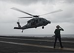 A U.S. Sailor salutes as an MH-60S Seahawk helicopter assigned to Helicopter Sea Combat Squadron (HSC) 6 takes off from the aircraft carrier USS Nimitz (CVN 68) in the Indian Ocean June 7, 2013 130607-N-LP801-098.jpg