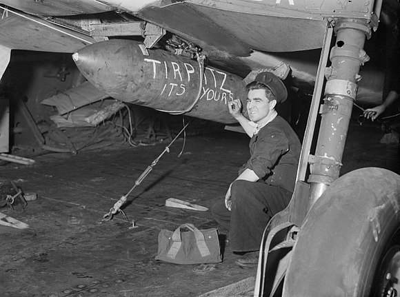 A sailor aboard HMS FURIOUS chalks a message on a bomb slung beneath an aircraft due to take part in the attack on the TIRPITZ in Alten Fjord, Norway, 3 April 1944. A22640.jpg