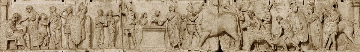 Relief depicts a long continuous scene that may be divided into three main groupings from left. The first is a group of four men wearing togas. Two are seated, and one is writing in a tablet. Two tall military guards divide this group from the central scene of sacrifice. Two musicians, markedly shorter than the soldiers, play a lyre and a horn. An unadorned altar, waist-high, stands in the center. To the viewer's left is the tallest figure in the composition, a military officer wearing a high plumed helmet and holding a long slender spear. standing by an altar. On the other side of the altar a priest, his head ritually covered, extends a libation bowl. A boy attendant pours from a pitcher into the bowl, and to that boy's right is a smaller boy looking on and lifting his right hand to the top of his head, a gesture that appears quizzical to modern viewers but may have some other significance in its Roman context. The priest is accompanied by a third boy close to his left side who stands ready with a towel. The right side of the relief is devoted to the procession of the three animal victims for the suovetaurilia, each led by a young male attendant, barechested but wearing a short kilt-like garment, with a wreath on his head. The first leads a enormous bull with a tasseled rope dangling from below its left horn. A fourth male attendant in the same attire follows closely on the bull's hindquarter, waving a palm branch in each hand. The attendant bringing the ram is followed by another veiled figure carrying a pole from which a banner unfurls. The attendant herding the pig is followed by another soldier bearing a long shield and looking back at another whose shield rests on the ground, covering most of his body. The last figure is a cavalryman, back turned to the viewer, next to his horse.