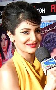 Anushka Sharma holding a mike and smiling away from the camera. She is dressed in a halter-neck yellow outfit.