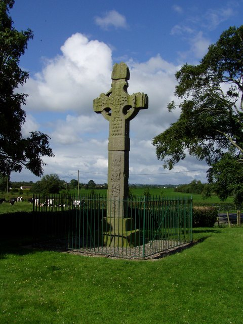 Tall stone cross, with intricate carved patterns, protected by metal railings surrounded by short cut grass. Trees are to either side, cows in open countryside are in the middle distance.