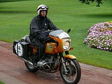 Gold BMW R90S motorcycle ridden through a park by a rider in black waterproof one piece suite