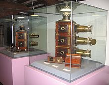 Two glass cabinets containing magic lanterns. On the left a bi-unial magic lantern by W.Tyler is displayed. The right-hand cabinet contains the J. H. Steward tri-unial mahogany magic lanterns with brass lenses.