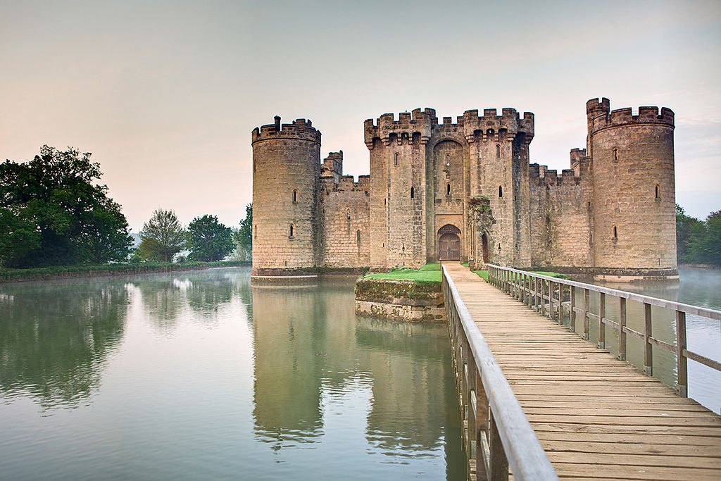 A long bridge leading to the gates of bodiam castle with its high walls and surrounded by a moat of water