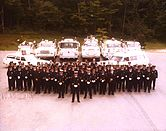 A fire department group photograph showing members and vehicles