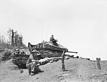 A main battle tank in a hull down position, its turret traversed to aft. In the foreground is a soldier kneeling.