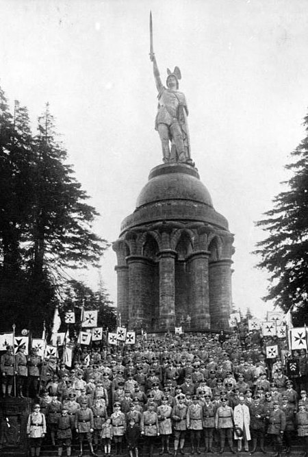 "An event of the Young German Order at the ""Hermannsdenkmal"" monument to Arminius, in 1925. At the time, Germans learned to see Arminius (often wrongly modernized into ""Hermann"") as a ""German"". Bundesarchiv Bild 118-30, Hermanns-Denkmal, Jungdeutsche Tagung.jpg"