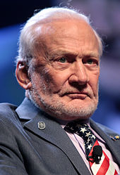 A stern looking Aldrin, with whispy white hair and a short, grey, stubbly beard. He wears an American flag tie with a microphone attached, and a lunar footprint pin on his right lapel. He wears a grey suit jacket with a pink dress shirt.