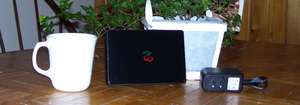 Cherrypal - Picture of Cherrypal C114, 110 V power adapter, coffee cup, and plant