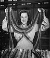 Canadian woman munitions worker shown covered with belts of 303 mm ammunition at plant in Quebec.jpg